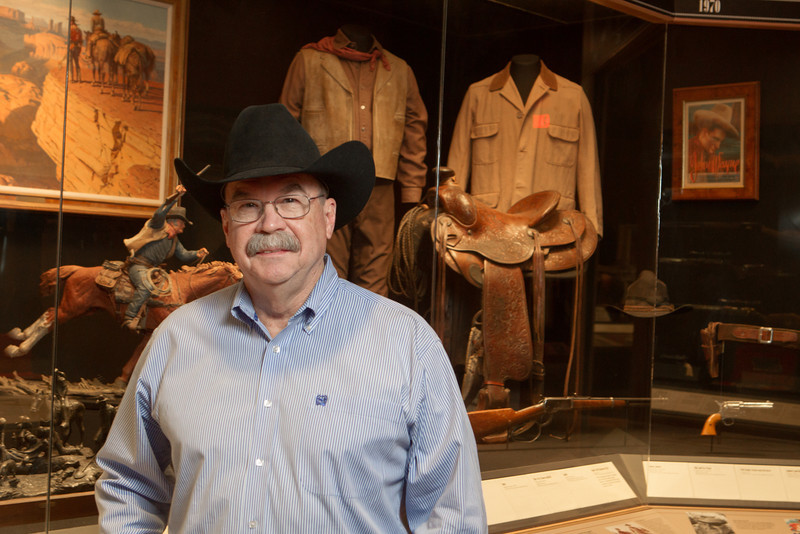 Don Reeves, curator for the National Cowboy and Western Hearitage Museum in Oklahoma City, stands in front of part of the John Wayne exhibit.