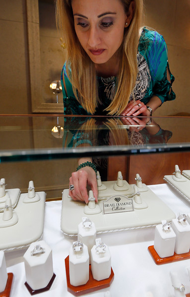 Lori Simms, Executive VP at Tulsa's Israel Diamond Supply, restocks the display case.