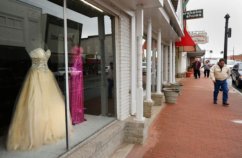 XXXX walks past a display of prom dresses in a downtown Tahlequah shop.