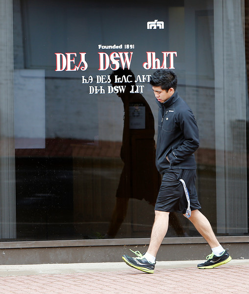 A pedestrian walks past signage written in the Cherokee language on a downtown Tahlequah bank window.