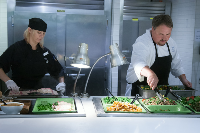 Laura Garmoe and Mark Vannasdall prepare the new healthier buffet area at Nebu in the Devon Tower.