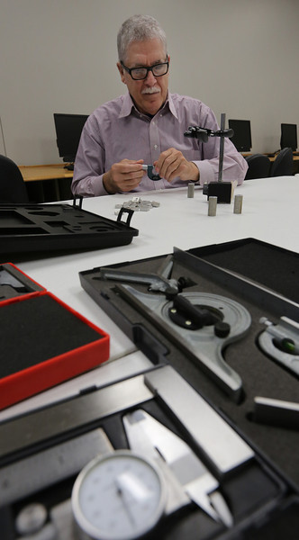 Michael Moore uses measuring equipment at the TCC  Workforce Development fast-track training class for entry level manufacturing jobs.