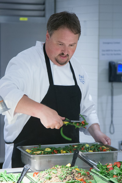 Mark Vannasdall prepares the new healthier buffet area at Nebu in the Devon Tower.