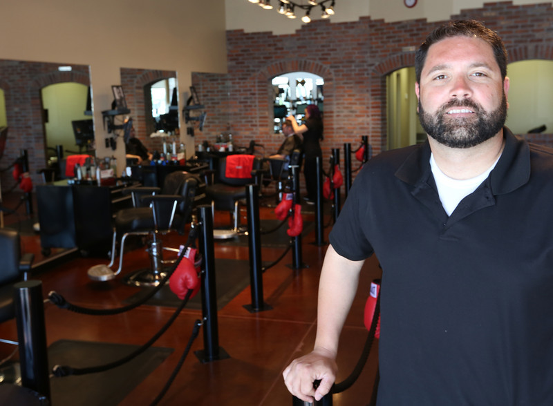 Knockouts franchisee Bob Conley pauses for a photo at his newly opened Broken Arrow sports-themed salon.