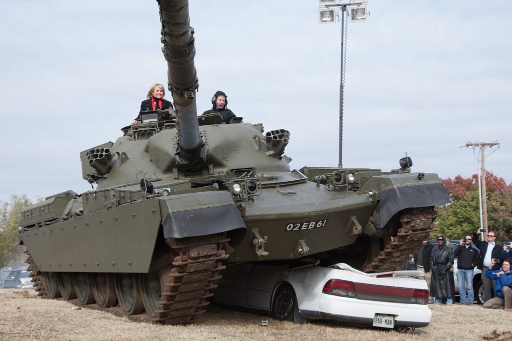 Gov Mary Fallin rides a tank over a car with owner Steve Hazelwood.