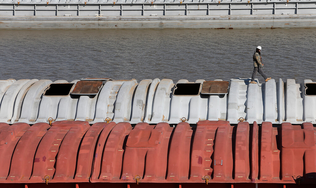 A crew member works inspecting barges on at the port of catoosa.
