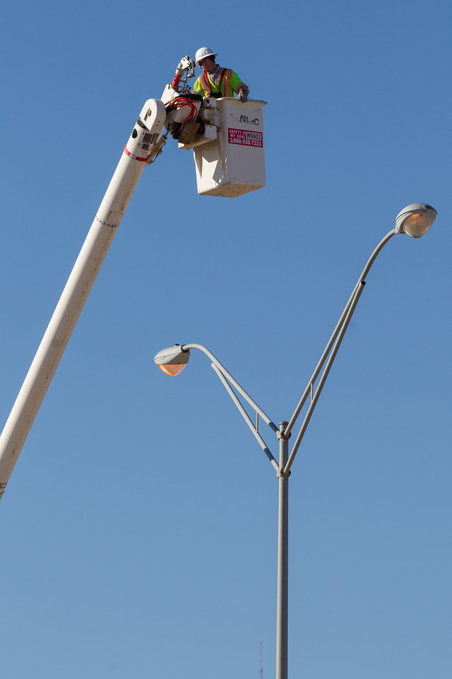A man manouvours high above I-35 to complete mantainance on a street light.
