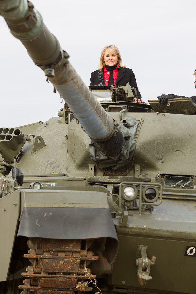 Governer Mary Fallin rides a tank over a car at the grand opening of Wilshire Gun in Oklahoma City.