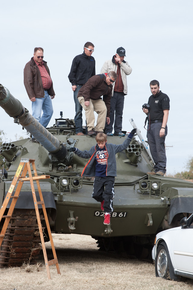 A kid jumps from a tank before the governer arrives for the ribbon cutting at Wilshire Gun in Oklahoma CIty.