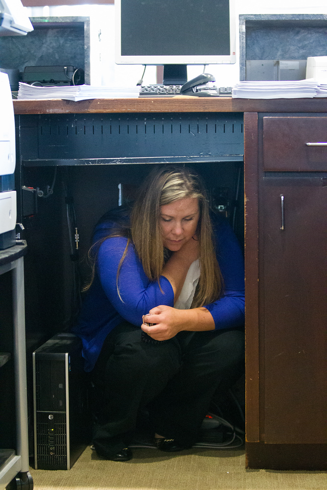 Ehrynn Shepard takes shelter during an earthquake drill at Bank of America in downtown Oklahoma City, OK.