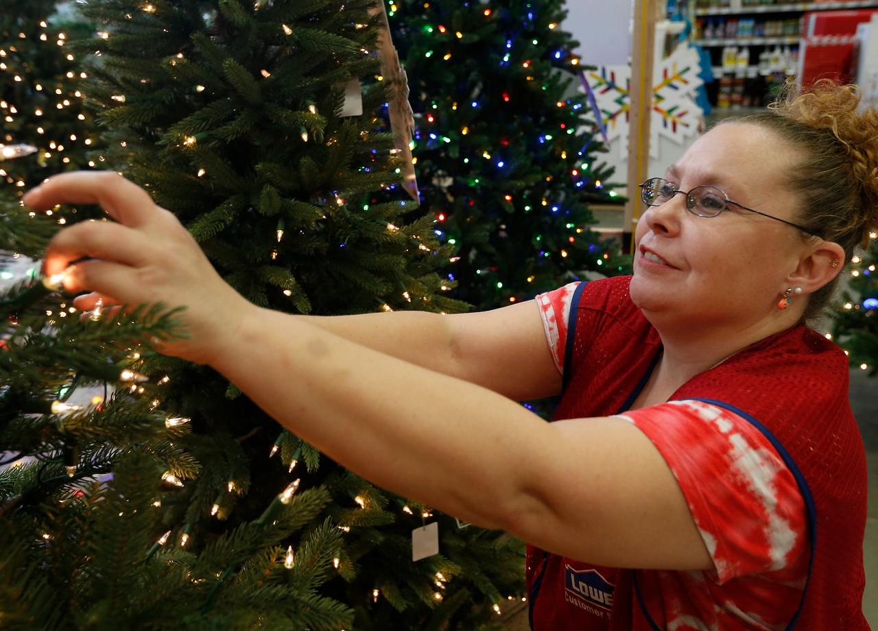 Lowe's sales associate Jean Morris works straightening up a  Christmas display in the companies Bixby store.