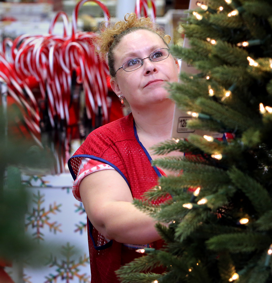 Lowe's sales associate Jean Morris works straightening up a  Christmas display in the companies Bixby store.