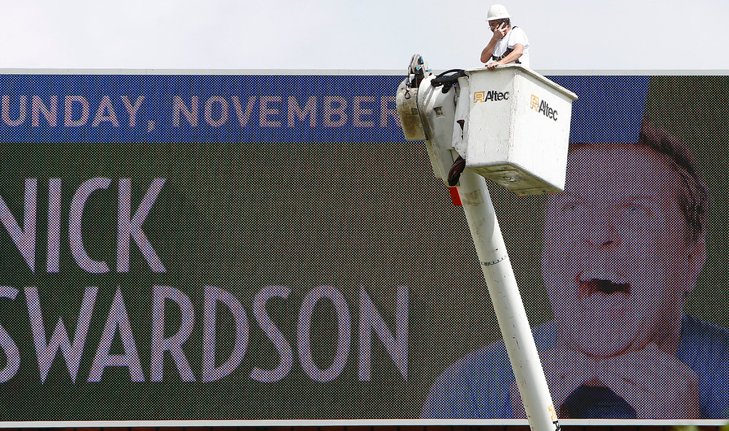 A repairman rides the lift on his bucket truck to work a billboard in south Tulsa.