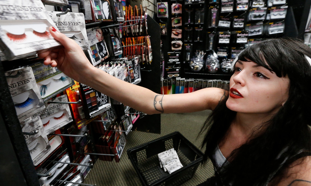 Spirit Halloween store employee Kari Mitchell stock the shelves in anticipation of the holidays sale rush.
