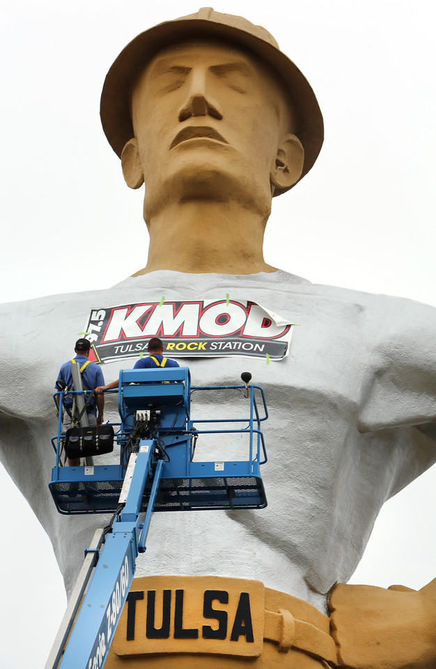Workmen dress up the golden driller in preparation for the Tulsa state fair.