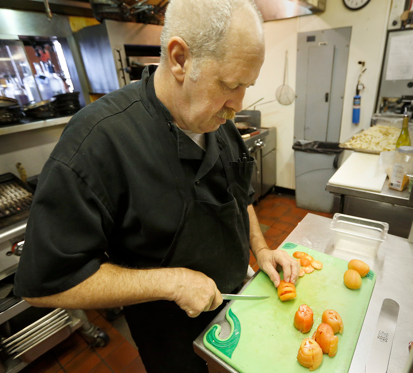 Dale Johnson prepares salads for a catered event at the Chalkboard restaurant in the Ambassador Hotel in Tulsa.