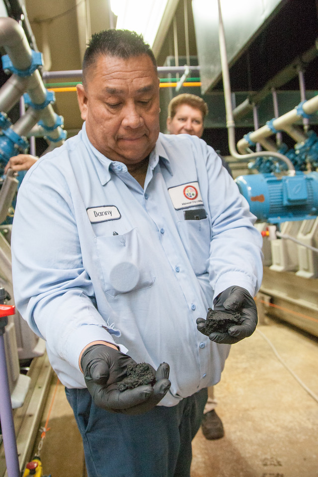Midwest City wastewater employee Danny Gray holds out a handful of biosolids, which is what's left after sewage is separated, treated and compressed.