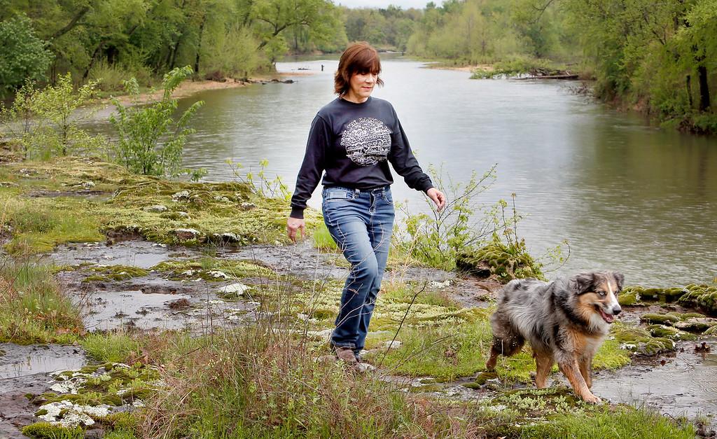 Denise Deason-Toyne, walks along the edge of the Illinois River near Tahlequah