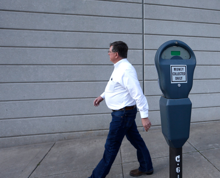 Attorney Kent Morlan walks past one of the many unused  parking meters in the Tulsa downtown area.