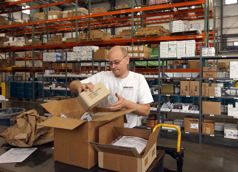 Mike Grimes packs up an order at the BlackHawk industrial shipping center in Broken Arrow.