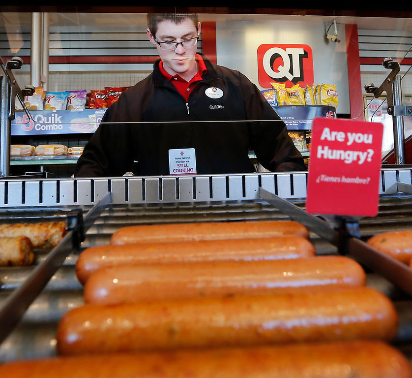 A Quik Trip employee loads that hot dog rollers in preparation for the lunch time rush.<br /> <br /> Grant  according to his badge