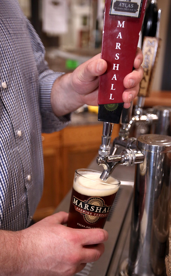Eric Marshall pours a beer in the Marshall Brewery showroom Tuesday afternoon. Senate Bill 424 would allow Oklahoma breweries, like Marshall's in Tulsa, to sell their sell their own beer on their premises.