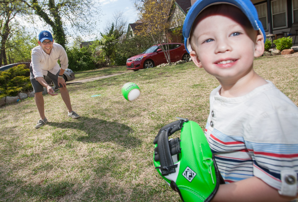 Lance Schmitz plays catch with his son Arlo in their front yard in Oklahoma City.