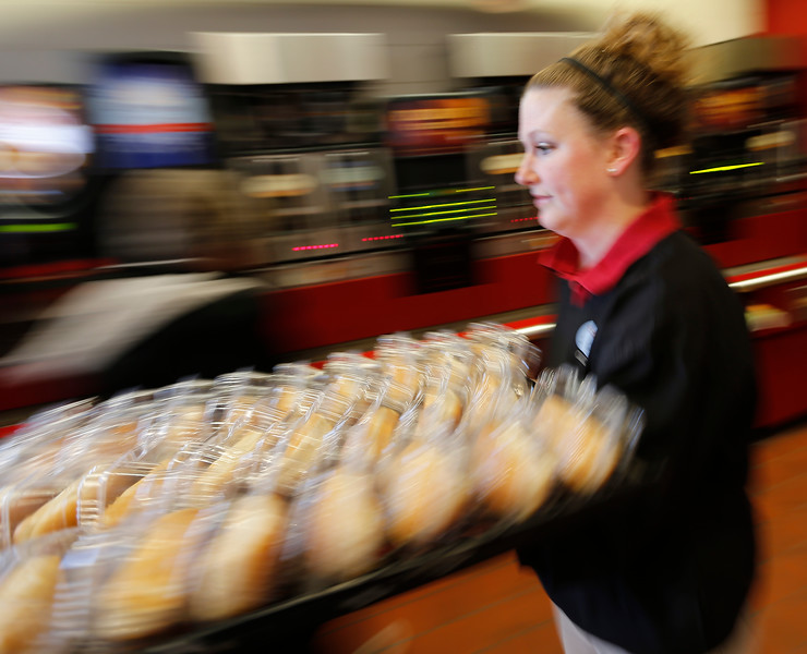 Quick Trip Assistant Manager brings a flat of hot dog buns from storage to display at the front of the store.<br /> <br /> Heather according to her badge