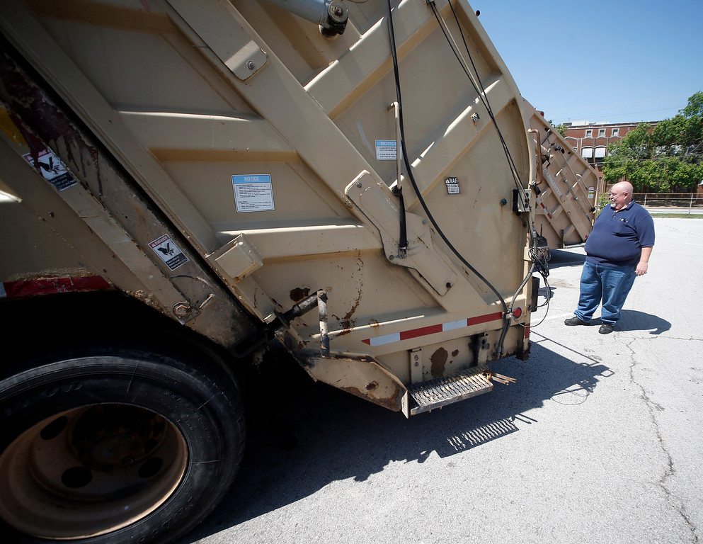 Cody Chezem, Surplus Coordinator for the City of Tulsa, inspects one of the many trash trucks being auctioned off Saturday by the city.