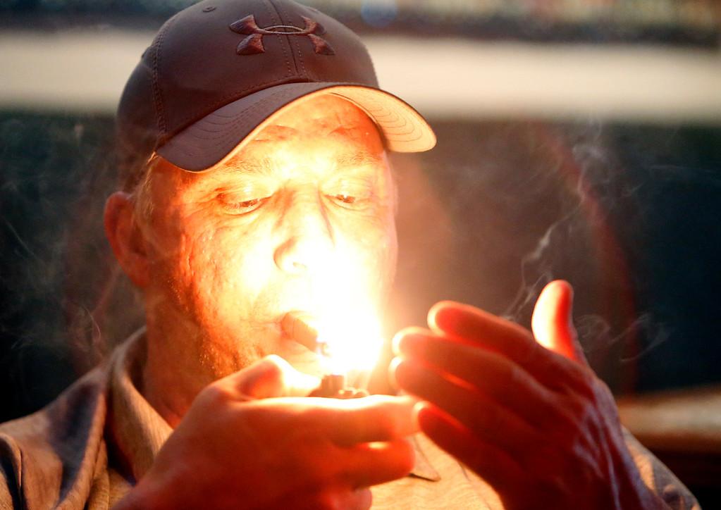 Sly nod lights his cigar at the Cigar Box in south Tulsa.