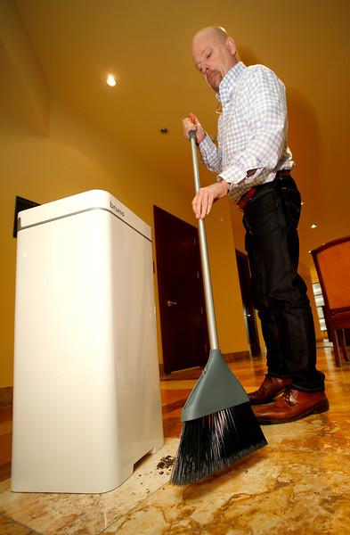 Jim Howard sweeps debris into the Bruno trash can.