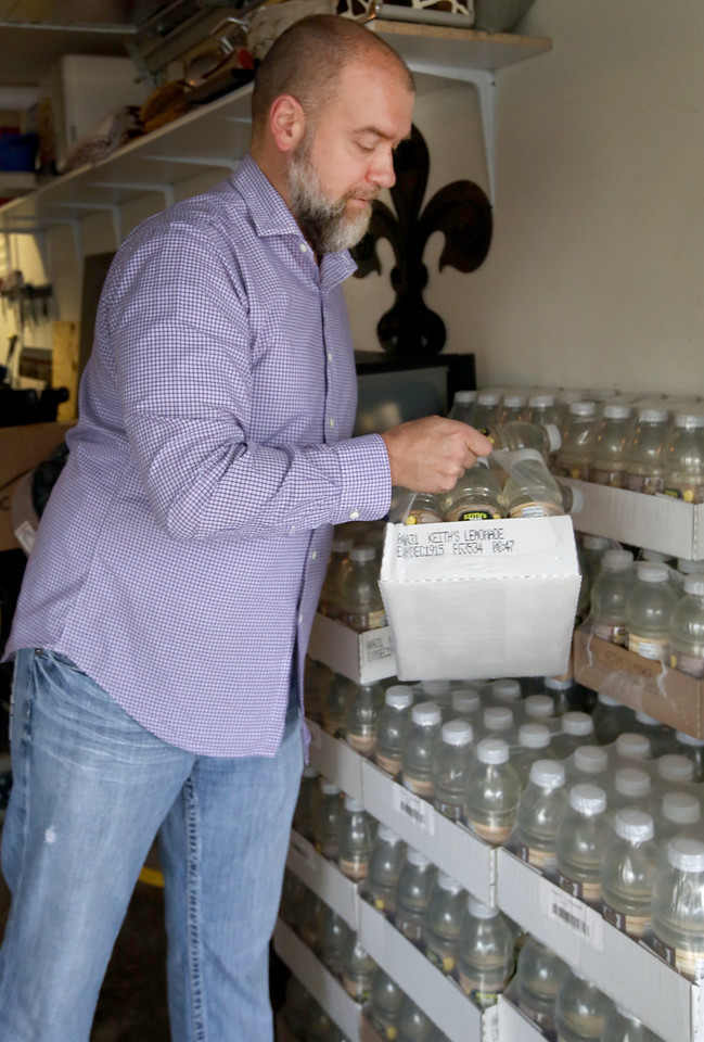 James Boyd, Operating head of Keith's Ice Cold Beverages, stacks a few extra crates of Keith's Ice Cold Lemonade against a wall at his Midtown Tulsa home.