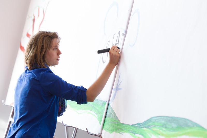 Melanie Ida Chopko adding to the collaborative mural for Disney at the Oklahoma Creativity Forum at the Civic Center in Oklahoma CIty.