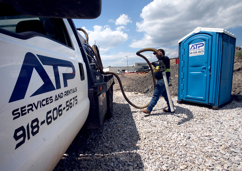 Aim to Please employee Frank Smith services a portable toilet at an construction site in Catoosa.