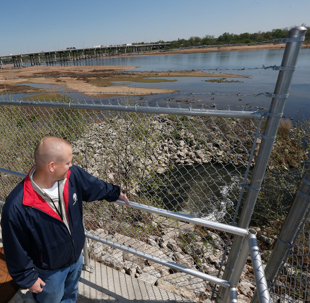 Matt Vaughan, Water Pollution Control Manager for theCity of Tulsa, looks at the discharging treated water entering the Arkansas River.