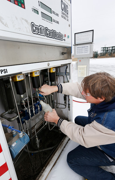 Tom Sewell, President of Tulsa Gas Technologies, clears a fuel filter on one of the companies CNG pumping stations.