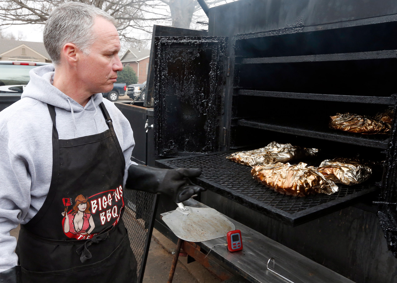 Bob Parker checks on the barbecued pork ribs he is cooking.