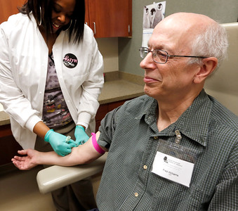 Tulsa's Cancer Treatment Center Phlebotomist Jamilah Wright draws blood from Fred Williams in preparation for his chemotherapy session on Saturday.