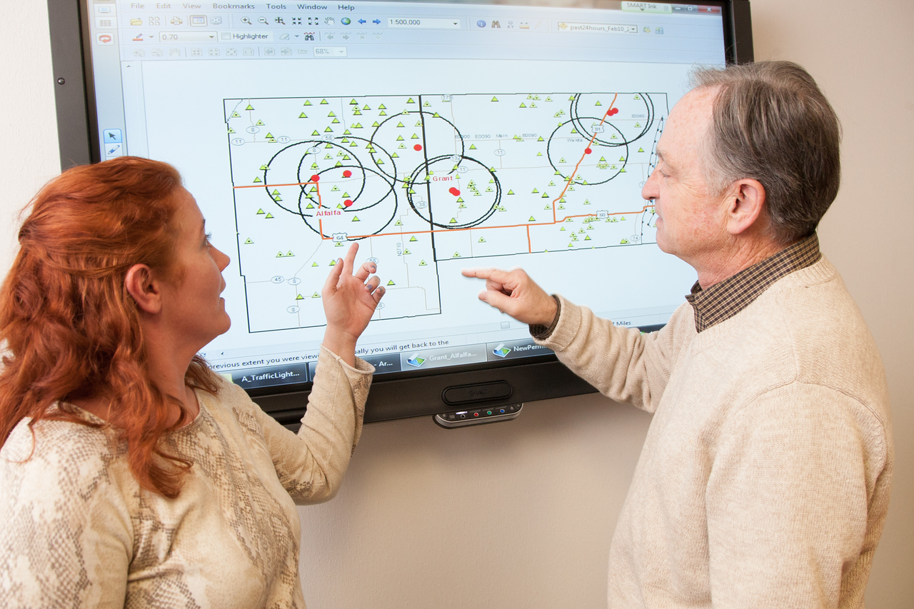 GIS analyst Kellie Duncan and Tim Bake, director of the oil and gas division of the Oklahoma Corporation Commision, using a map showing earthquakes and waste water dispel sites.