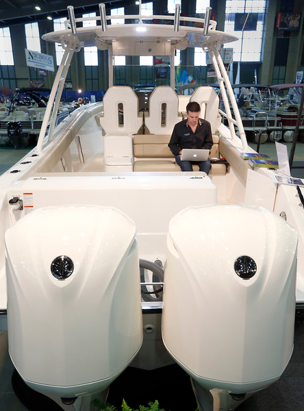 Brad Williams of Williams Yacht Group works his e-mail while sitting on a  Pursuit 310 boat on display at the 2015 Tulsa Boat Sport & Travel Show.