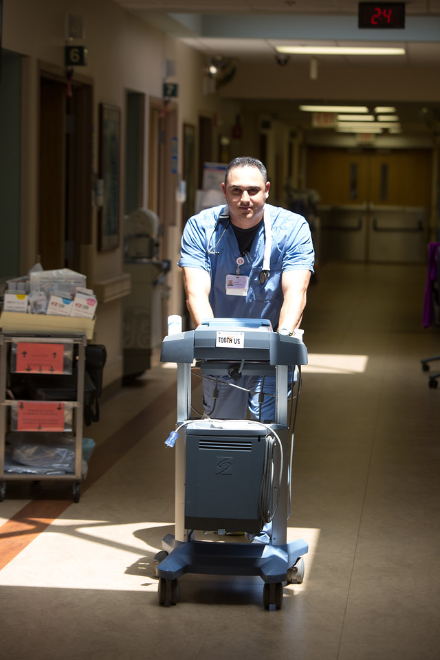 Michael Fusselman pushing an ultrasound machine at Norman Regional Hospital.