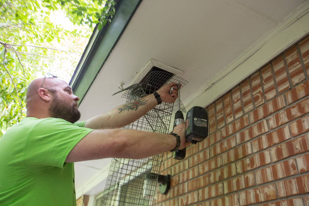 Justin Kafitz, with The Skunk Whisper pest controll, removes a trap from a customer's house in Norman, OK.