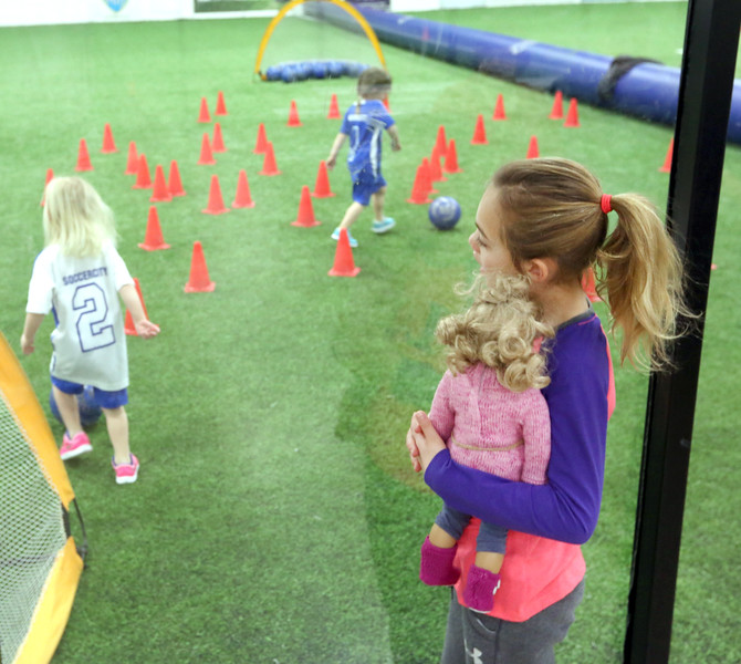 During a snow day in Tulsa eight year old Savannah (right) checks out her sister working the obstacle course at an indoor Soccer City's indoor fields.