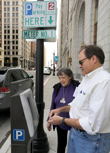 Joan and Jeremy Jackson feed quarters into a parking meeter in downtown Tulsa.