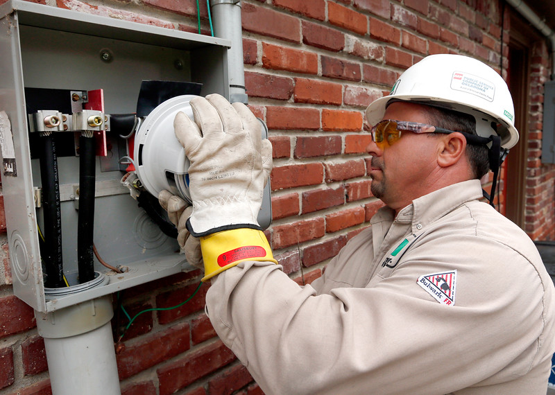 PSO contractor Rick Sabot installs a new residential electric meter on a house in Tulsa.