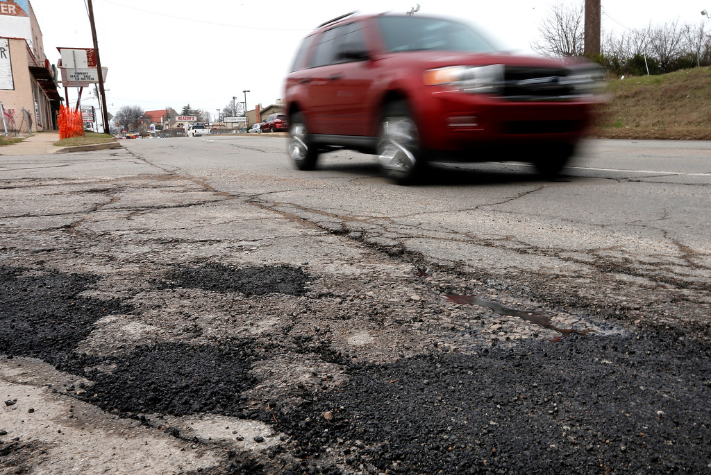 Tulsa drivers dodge around one of the thousands of potholes that dot the city.