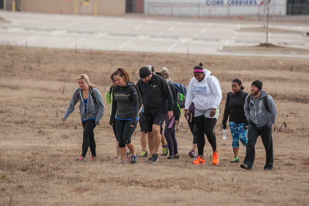Sean Shearon (right) leads a class training for the Memorial Marathon in Oklahoma City by wearing weighted backpacks.