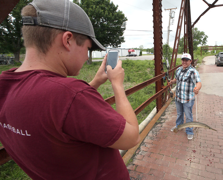 Hayden Vernon grabs a cell phone photos of Randy Chavez with an alligator gar the friends speared while bow fishing off the Rt66 Bridge West of Sand Springs.
