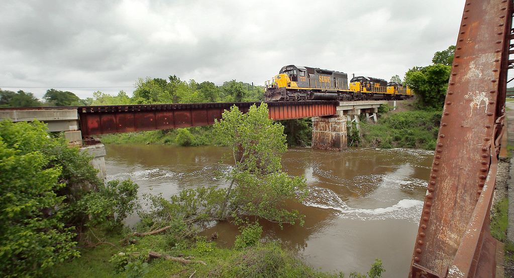 A Stillwater Central Railroad freight train crosses a rain swollen stream West of Sand Springs.