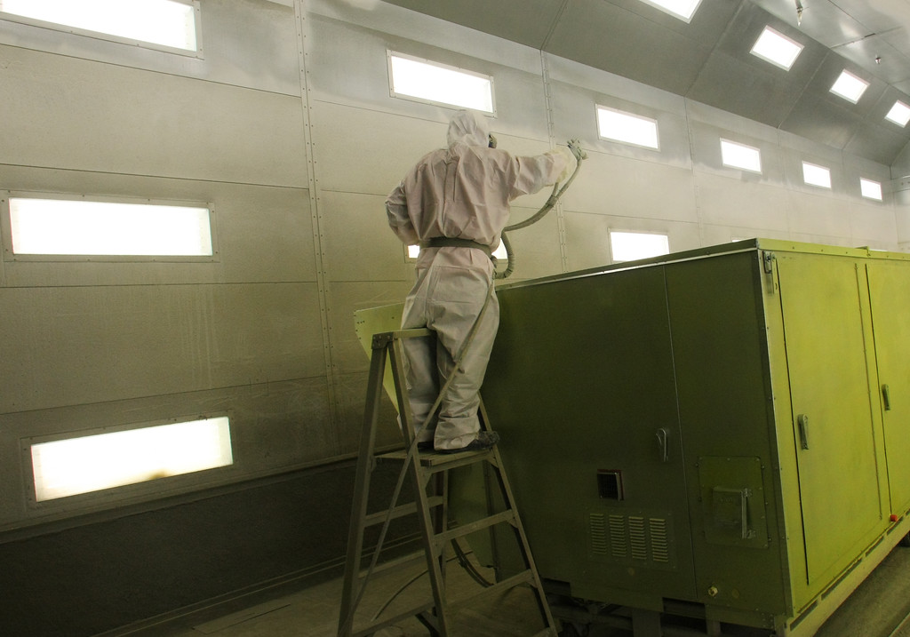 An AAON employee sprays a coat of paint onto an industrial Air-Conditioning unit at the companies Tulsa manufacturing plant.
